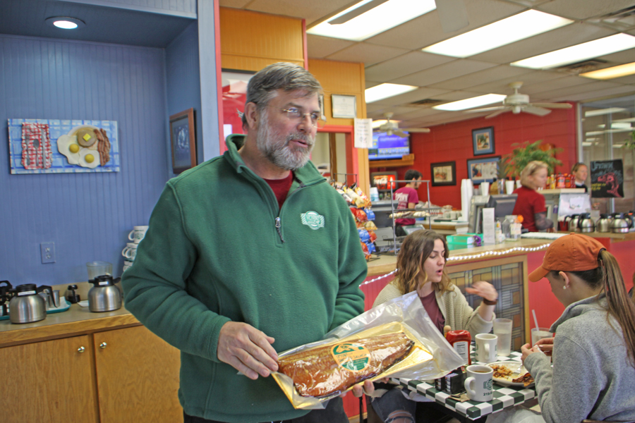 owner at Uptown Cafe showing guests a salmon in Tallahassee, FL