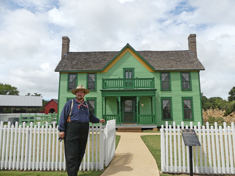 Docent stands at gate in front of farmhouse and welcomes visitors at Nash Farms