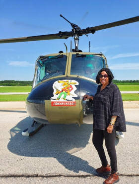 Woman standing n front of Huey Heliocopter