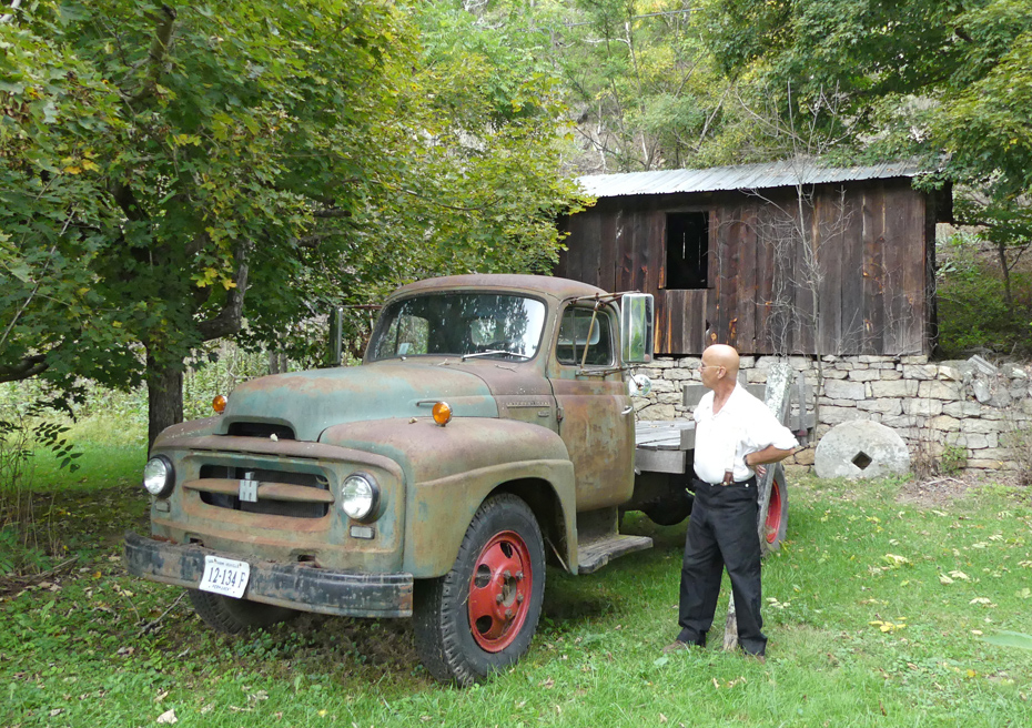 Man  next to antique truck parked in front of  Blacksmith Shop.