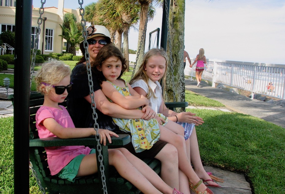 woman with three young girls sits on swing near beach