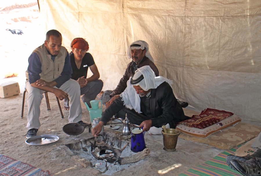 four Bedouin men in a tent brewing coffee at Wadi Feynan